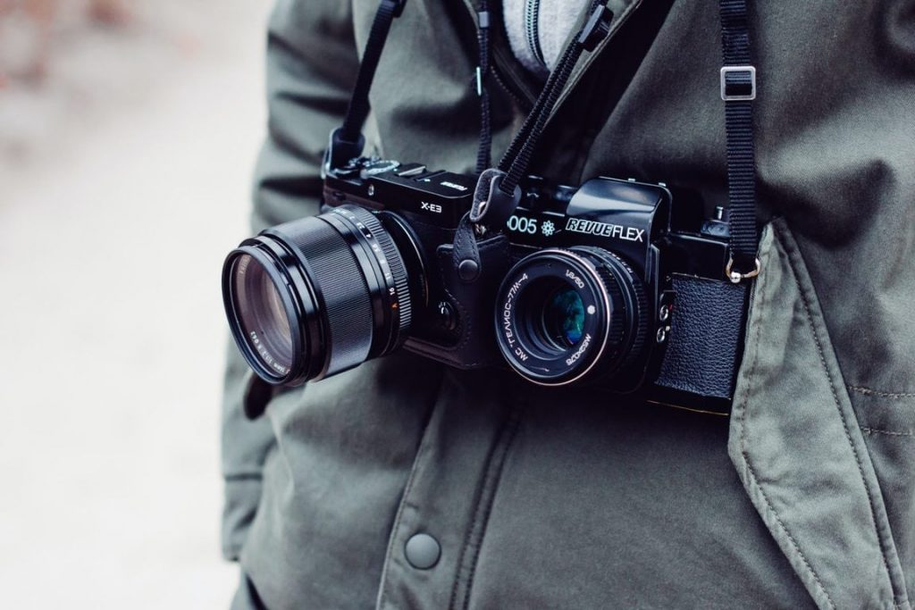person with two black DSLR cameras