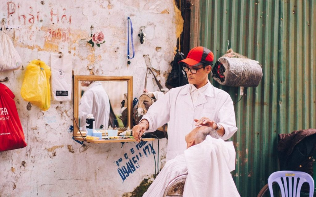 man in white shirt with red cap sits beside vanity mirror on wall