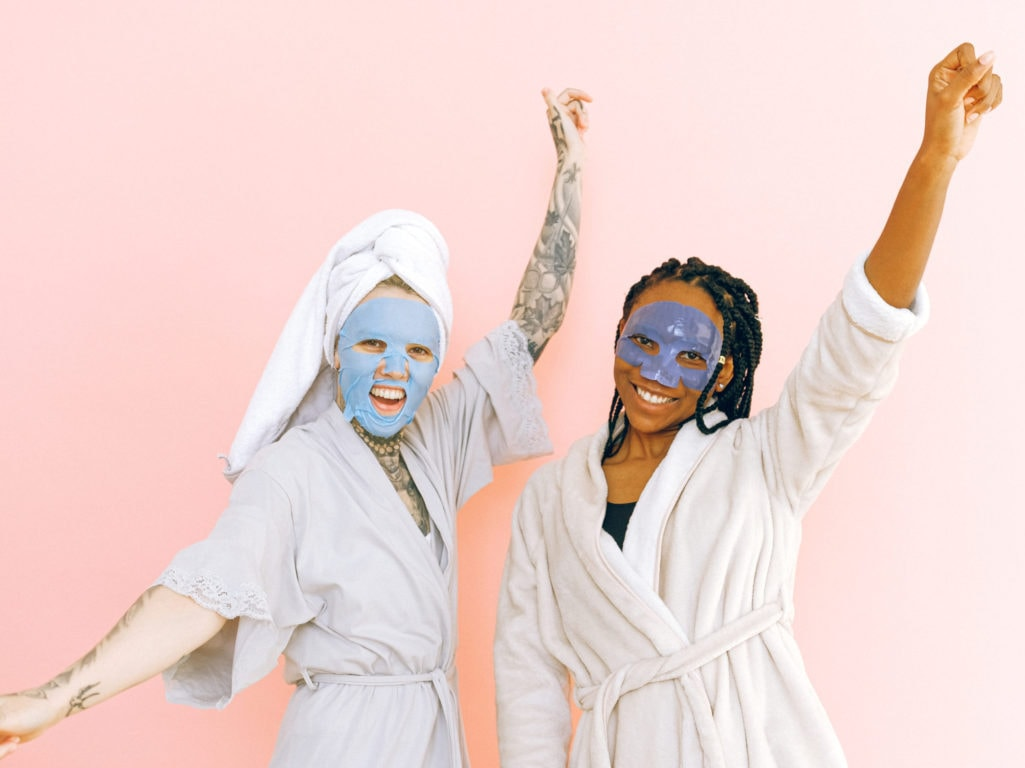 Content multiracial female friends in cosmetic masks raising hands