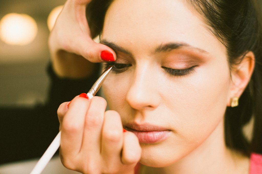 Crop stylist drawing eyeliner on model eyelid