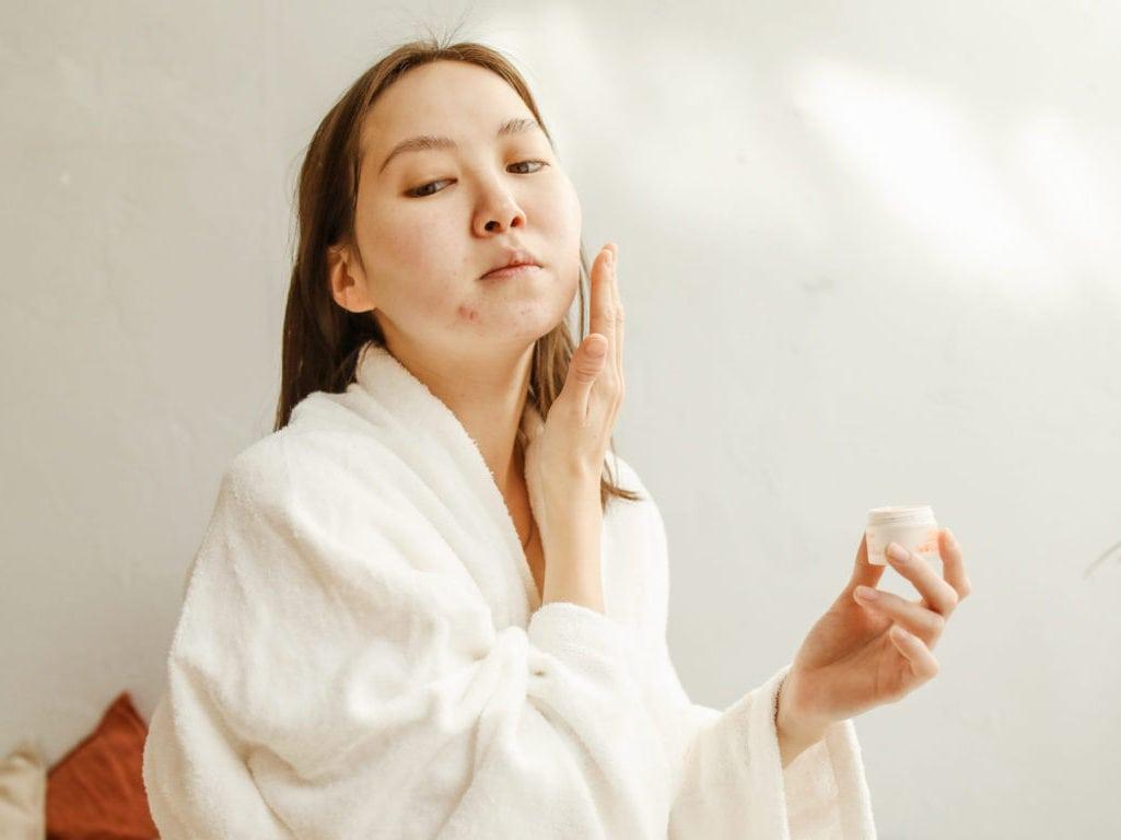 Woman in white robe holding white ceramic mug