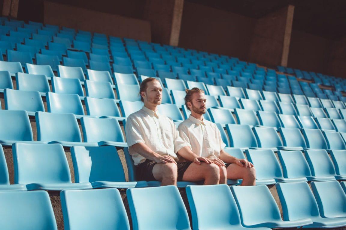 Serious men sitting on chair on stadium